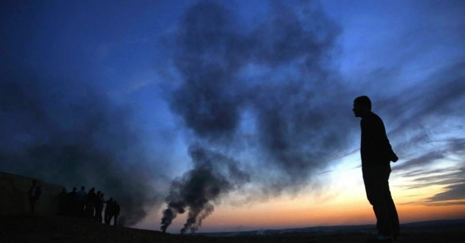 27.out.2014 - Refugiados curdos olham do alto de uma colina as explosões na cidade síria de Kobani, entre a fronteira da Turquia e a Síria, durante fortes combates entre o grupo Estado Islâmico (EI) e forças curdas neste domingo (26).  Ao todo, 815 pessoas morreram em 40 dias de ofensiva do EI contra o enclave curdo sírio de Kobani, informou o Observatório Sírio de Direitos Humanos
