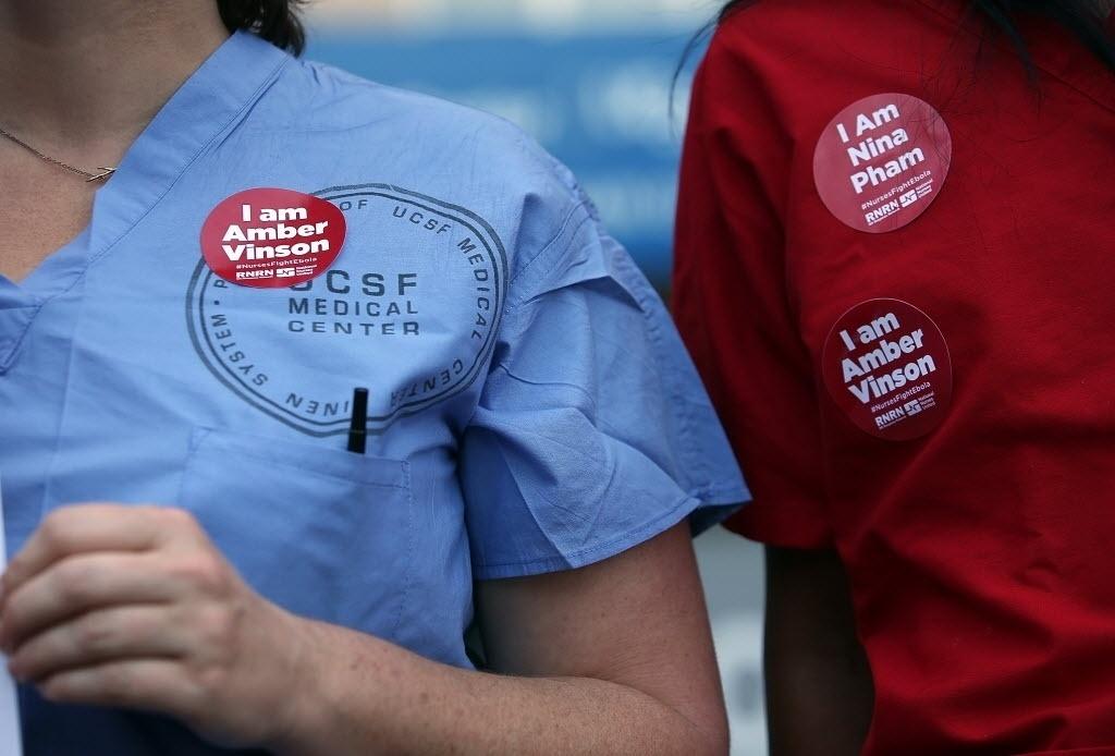 28.out.2014 -  Durante ato contra falta de estrutura para receber pacientes com o vírus ebola, enfermeiras do Centro Médico da Universidade da Califórnia usam adesivos em apoio à enfermeira americana Amber Vinson, a segunda a contrair a doença enquanto cuidava de um paciente liberiano no Texas