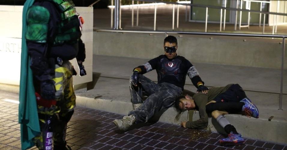 28.out.2014 - Sob observação do Mr. Extremo (esq.), Fallen Boy auxilia mulher enquanto esperam chegada de ambulância durante a madrugada de San Diego, na Califórnia. Fundado pelo Mr. Extremo em 2006, o grupo de voluntários utiliza identidades secretas para patrulhar as ruas da cidade americana, oferecendo assistência para quem necessitar