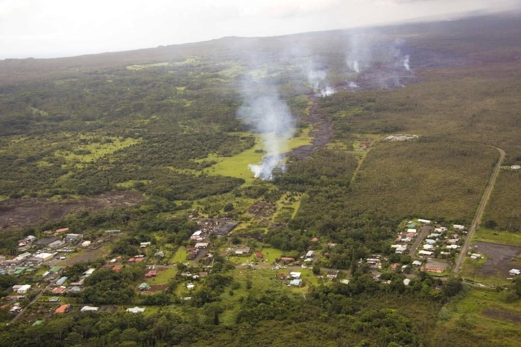 28.out.2014 - Um fluxo ameaçador de lava chegou nesta terça-feira (28) ao terreno de uma propriedade, ameaçando destruir uma casa, disseram autoridades. A lava, que corre lentamente do vulcão Kilauea, avança há semanas na cidade de Pahoa, no Havaí, e os residentes locais já foram avisados para se preparar para uma retirada. A imagem foi tirada nessa segunda-feira (27) e divulgada na terça (28)