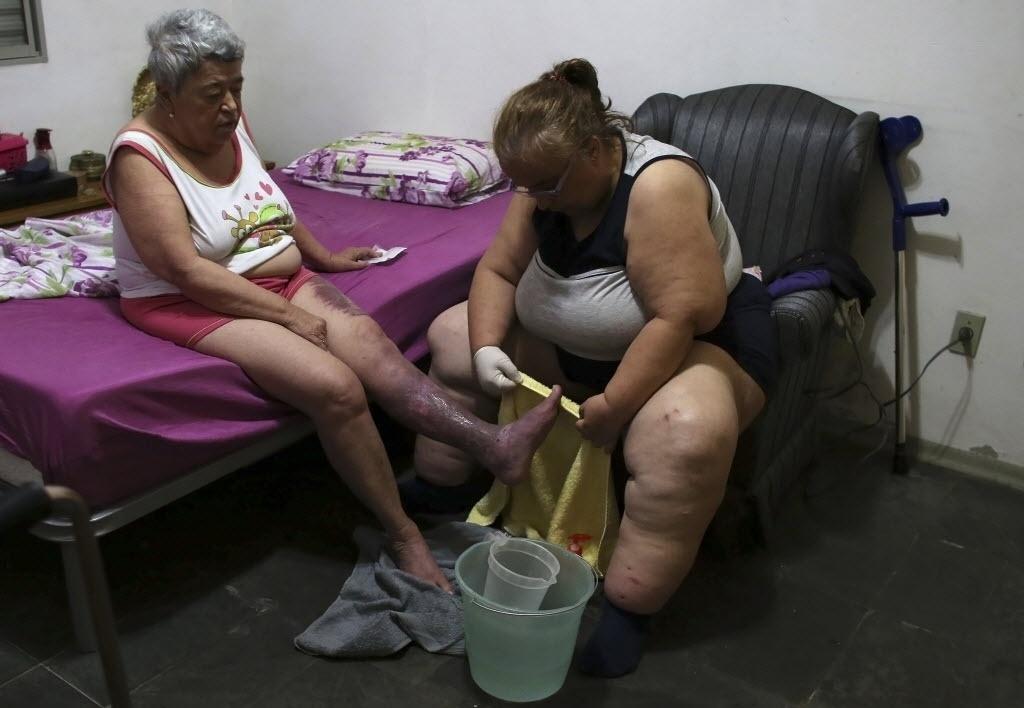 29.out.2014 - Ana Paula, 44 anos, lava os pés de sua mãe Lúcia, 70 anos, que sofre da doença erisipela bolhosa, usando água coletada de fora da sua casa devido ao racionamento de água em Itu, a 101 km de São Paulo. Devido à falta de água nas residencias, a prefeitura da cidade instalou caixas d'água para abastecer a população