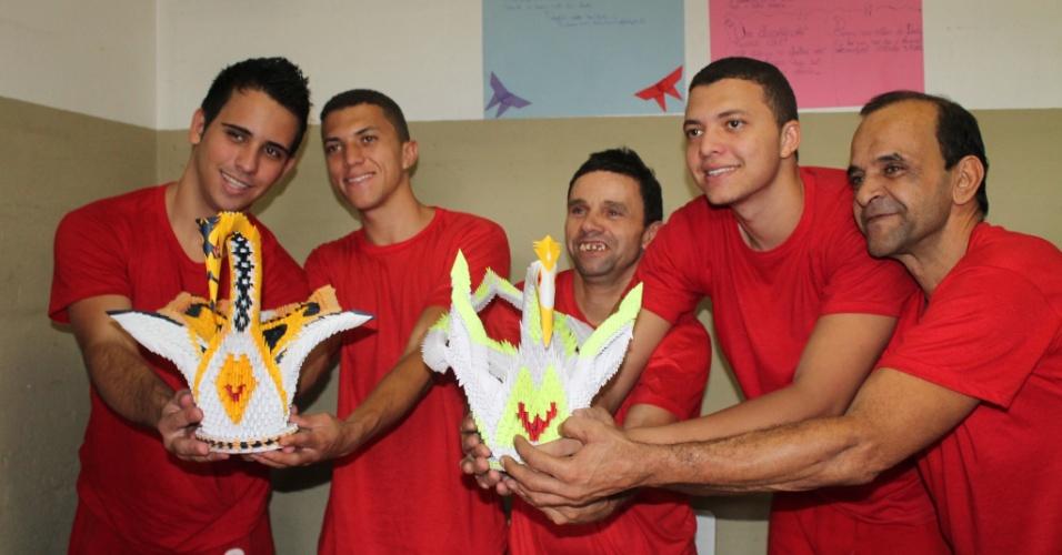 29.out.2014 - Detentos do Ceresp (Centro de Remanejamento do Sistema Prisional) de Betim (MG), na região metropolitana de Belo Horizonte, que participam da oficina de origami, mostram duas de suas criações