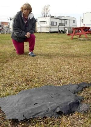 Mulher se ajoelha ao lado de um pedaço do foguete Antares na Virgínia (EUA)