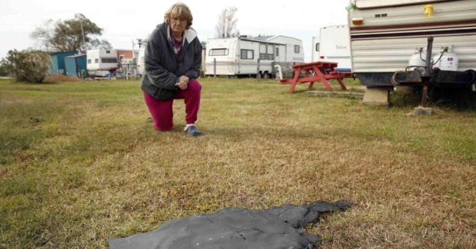 29.out.2014 - Sandy Saxby se ajoelha ao lado de um pedaço do foguete Antares na cidade de Chincoteague, na Virgínia (EUA). Nesta terça-feira à noite, o foguete Antares, de 14 andares, explodiu durante o lançamento na ilha Wallops, vizinha a cidade
