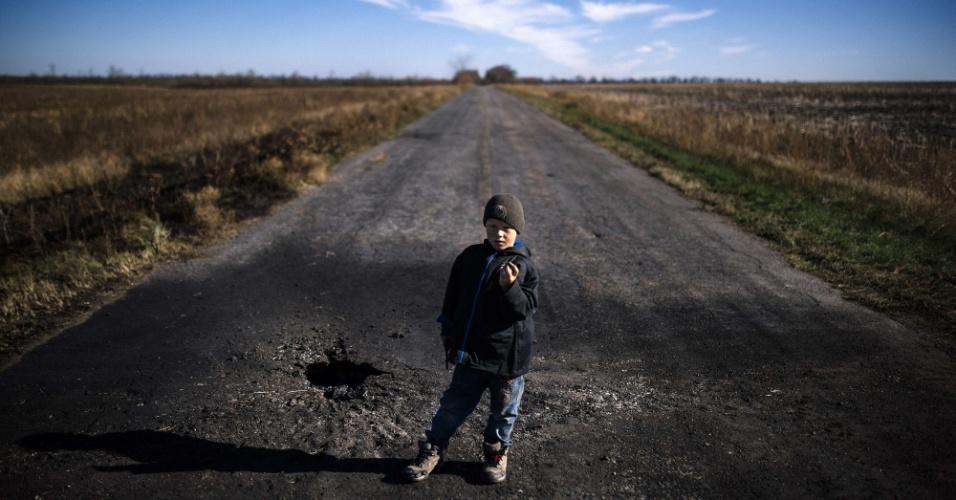 29.out.2014 - Um garoto mostra estilhaços de próximo de um buraco feito por morteiro no vilarejo de Naberezhne, no leste da Ucrânia, nesta quarta-feira (29). O secretário-geral da ONU, Ban Ki-moon, lamentou os planos dos rebeldes separatistas ucranianos de realizar eleições neste fim de semana, dizendo que urnas minaram os acordos de paz