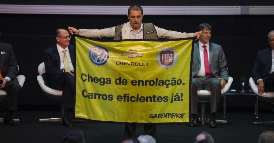 30.out.2014 - Manifestante do Greenpeace protesta contra a eficiência dos carros nacionais durante a cerimônia de abertura do Salão Internacional do Automóvel 2014, no Pavilhão do Anhembi, nesta quinta-feira (30). Ao fundo, o prefeito Fernando Haddad (à dir.) e o governador Geraldo Alckmin (à esq.)