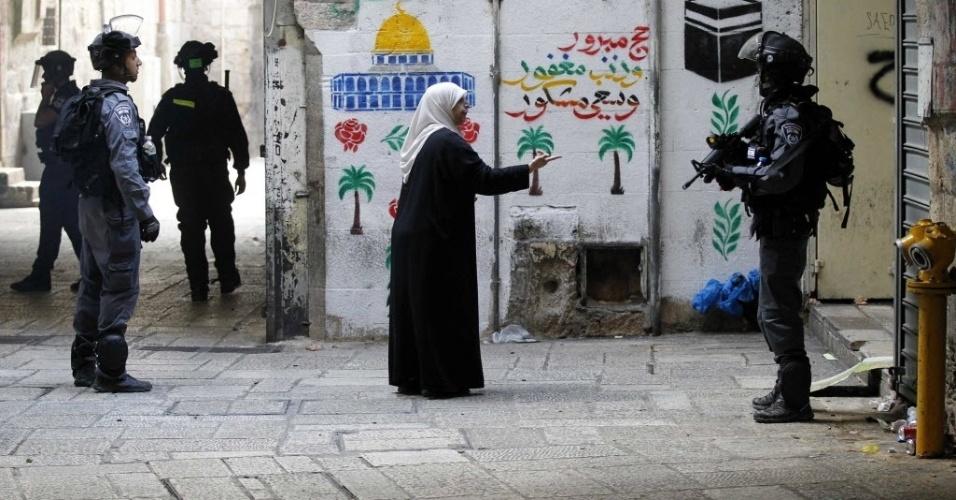 30.out.2014 - Mulher palestina conversa com policial israelense na cidade velha de Jerusalém, em Israel. A polícia israelense matou um palestino suspeito de envolvimento na tentativa de assassinato do rabino Yehuda Glick, ativista que foi gravemente ferido a tiros na noite desta quarta-feira (29)