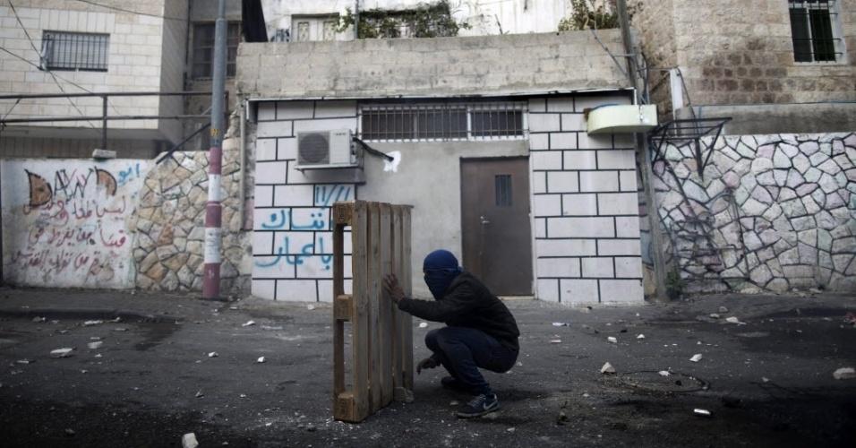 30.out.2014 - Palestino se protege com tábuas durante confronto com as forças de segurança israelenses em Jerusalém Oriental (Israel). A polícia israelense matou um palestino suspeito de envolvimento na tentativa de assassinato do rabino Yehuda Glick, ativista que foi gravemente ferido a tiros na noite desta quarta-feira (29)