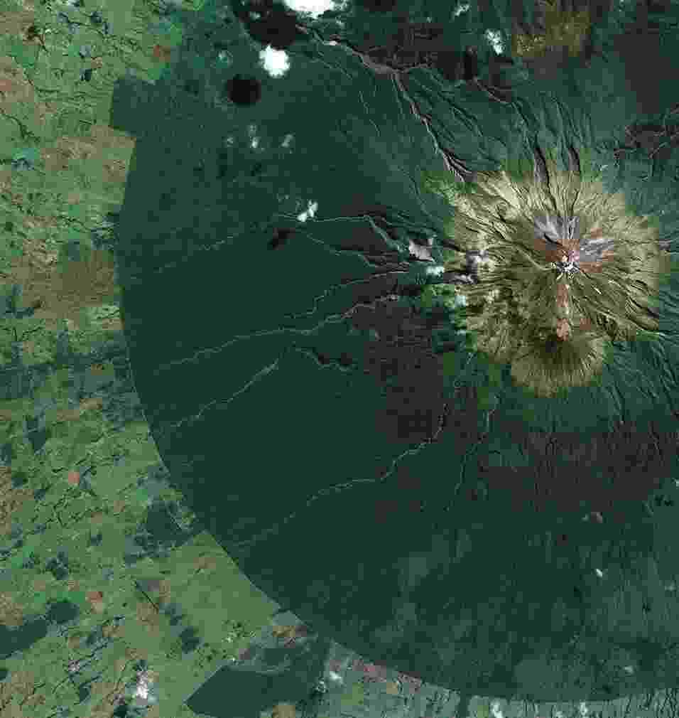 31.out.2014 - Parque Nacional Egmont em North Island, na Nova Zelândia, é visto através de satélite. A fronteira entre as áreas protegidas e não protegidas pode ser vista de forma clara na imagem: a parte densamente florestada é a área verde escura, e a paisagem agrícola aparece na tonalidade mais clara. A montanha no centro do parque nacional tem dois nomes: Monte Egmont e Monte Taranaki. Taranaki é o nome original dado pelo povo indígena Maori, enquanto o nome Egmont foi dado pelo explorador britânico James Cook, em 1770. A montanha é considerada um vulcão ativo, embora tenha ficado dormente por mais de 150 anos - KARI/ESA