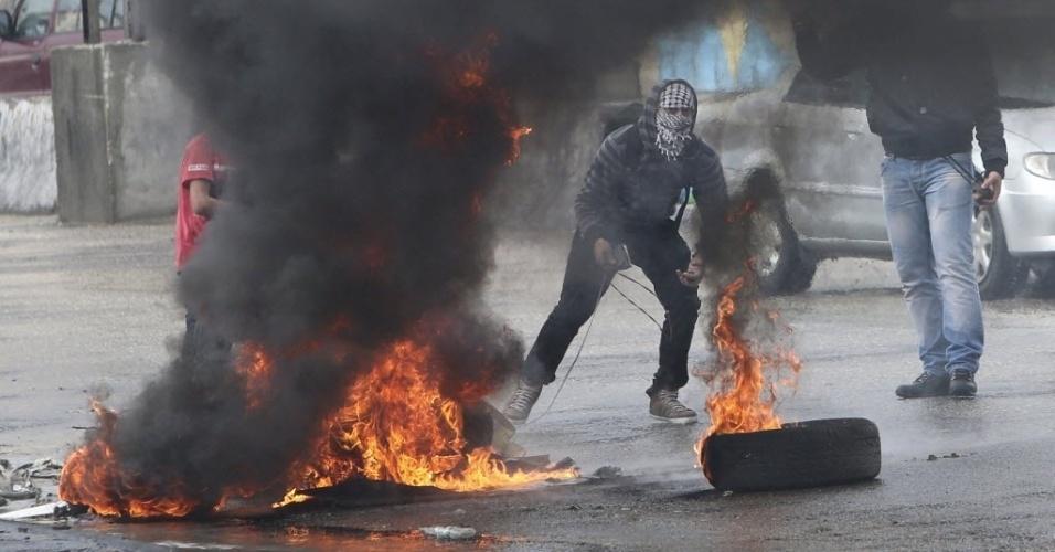 31.out.2014 - Manifestante mascarado lança pedra contra forças israelenses após manifestação anti-Israel em Ramallah, na Cisjordânia. Palestinos protestam contra o fechamento por Israel dos acessos à Esplanada das Mesquitas, local sagrado para os muçulmanos