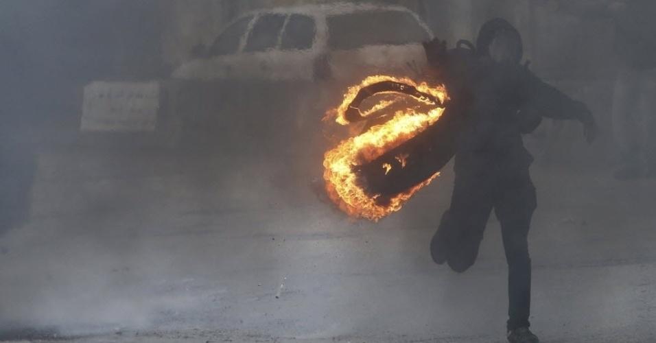31.out.2014 - Manifestante mascarado lança pneu em chamas contra forças israelenses após manifestação anti-Israel em Ramallah, na Cisjordânia. Palestinos protestam contra o fechamento por Israel dos acessos à Esplanada das Mesquitas, local sagrado para os muçulmanos
