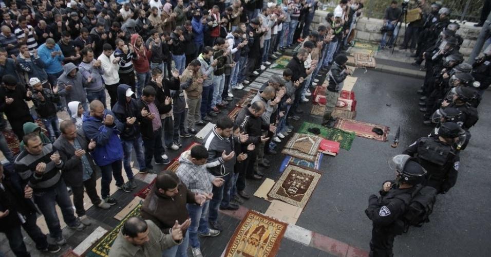 31.out.2014 - Palestinos rezam diante de forças de segurança israelenses em acesso bloqueado à Esplanada das Mesquitas, na entrada da cidade antiga de Jerusalém. Israel está controlando a passagem pelo local em medida tomada na quinta-feira (30) após atentado que deixou mortos um judeu de ultradireita e o palestino suspeito pelo ataque. Apenas mulheres e homens com mais de 50 anos puderam passar pelo bloqueio, que visa coibir protestos. Sexta-feira é dia de orações para os muçulmanos, o que faz com que a Esplanada das Mesquitas, local sagrado para o Islã, fique cheia