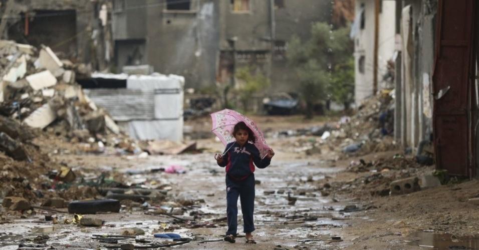 3.nov.2014 - Menina palestina segura um guarda-chuva enquanto caminha pelas ruínas de uma casa que foi destruída por um bombardeio israelense, durante o conflito mais recente entre Israel e o Hamas, em um dia chuvoso no leste da Cidade de Gaza