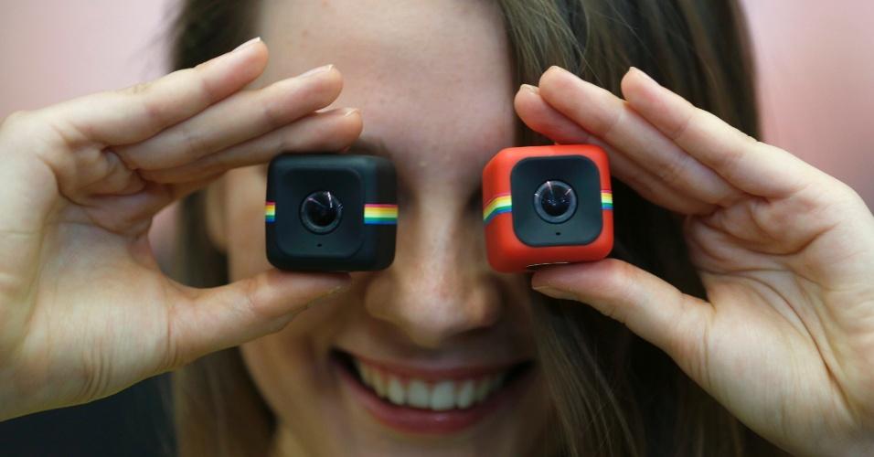 """4.nov.2014 - A Polaroid lança a sua primeira câmera digital """"lifestyle action"""". Nomeado Cube, o lançamento conquista usuários pelo formato divertido (um cubo de 3,5 cm² envolto em uma faixa clássica da marca e disponível nas cores preta, vermelha ou azul) e pela resistência a quedas, batidas e água. Por outro lado, o preço sugerido de R$ 670 e os barulhos irritantes a cada ação são bem pouco agradáveis"""