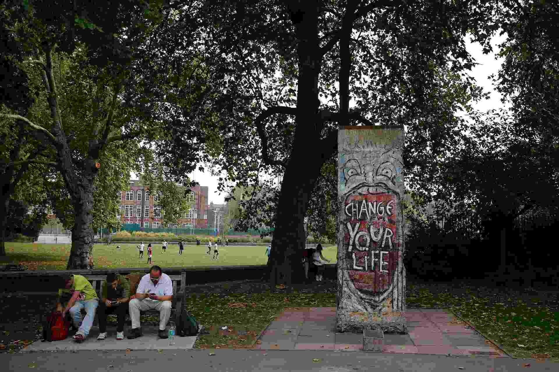 """18.set.2014 - Homens se sentam em banco ao lado de um trecho do Muro de Berlim na área externa do Imperial War Museum, em Londres. Este segmento foi retirado de perto do Portão de Brandemburgo, em Berlim, e contém um grafite do artista Indiano que diz """"Mude sua vida"""". Após a queda do muro, cujo aniversário de 25 anos é celebrado neste ano, pedaços da construção se espalharam por países ao redor do mundo - Stefan Wermuth/Reuters"""