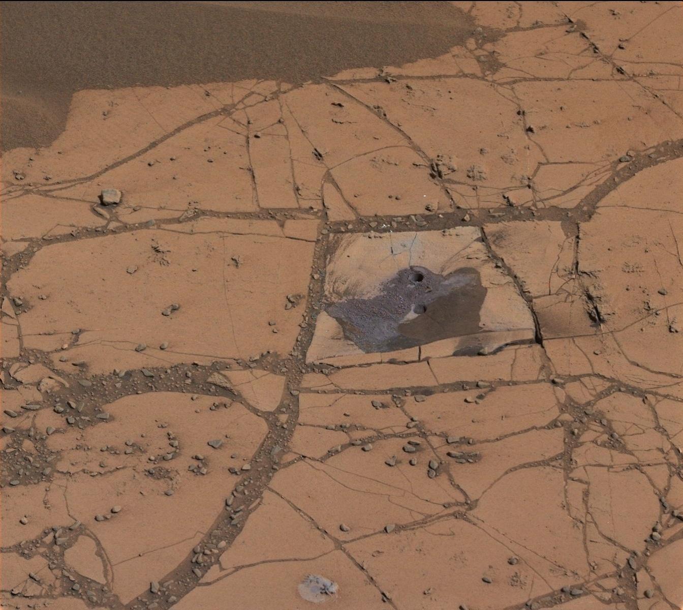 5.nov.2014 - PERFURAÇÃO EM MARTE - Imagem mostra primeira perfuração do robô Curiosity, da Nasa (agência espacial americana), no monte Sharp, em Marte. Na ocasião, o robô encontrou um pó de rocha avermelhado com mais hematita do qualquer outra amostra obtida por ele ao longo da missão, que já completa dois anos.A hematita, um mineral de óxido de ferro, dá pistas sobre as condições ambientais do planeta durante sua formação e já havia sido mapeada antes mesmo do robô pousar no planeta vermelho