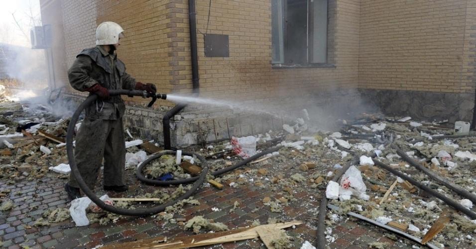 5.nov.2014 - Um bombeiro apaga fogo de uma casa danificada após bombardeio em Donetsk, nesta quarta-feira (5), na Ucrânia. Dois civis, entre eles um adolescente de 14 anos, morreram nessa quarta com bombardeios em um campo de esportes de uma escola em Donetsk, leste rebelde da Ucrânia, segundo jornalistas da AFP