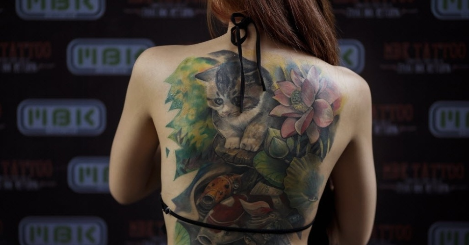 23.out.2014 - Uma competidora do Concurso MBK de Tatuagem, realizado em um shopping center de Bancoc, mostra suas tatuagens na Tailândia