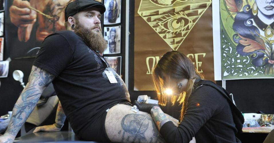 7.nov.2014 - Tatuador trabalha durante a convenção de tatuagem realizada em Bruxelas, na Bélgica