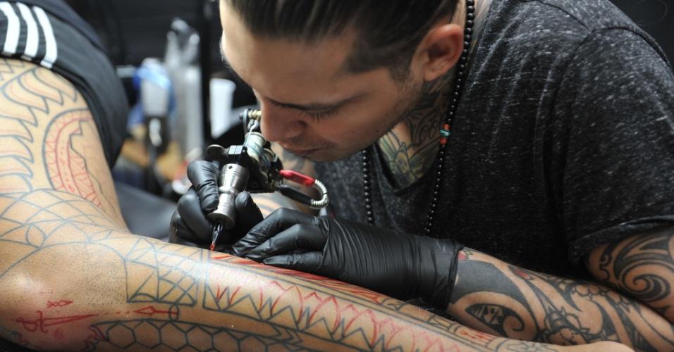 7.nov.2014 - Tatuador trabalha na criação de uma tatuagem durante convenção realizada em Bruxelas, na Bélgica