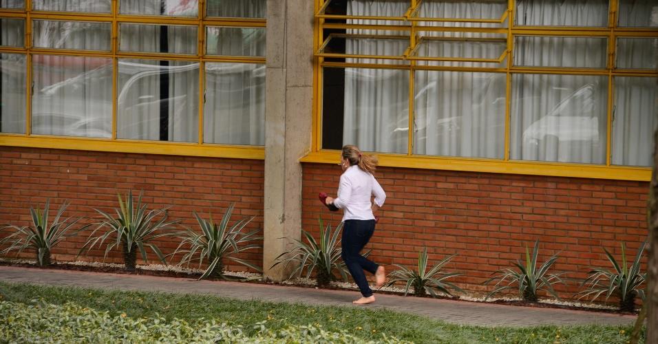 8.nov.2014- A candidata Claudia Campoi Romã, 40, corre descalça para tentar chegar a tempo para a prova do Enem, no campus da PUC-PR, em Curitiba