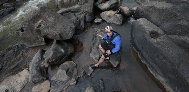 O instrutor de rafting Augusto Rodrigues Bazani, 23, senta no leito seco de corredeira de rio em Socorro, no interior de São Paulo - Joel Silva/ Folhapress