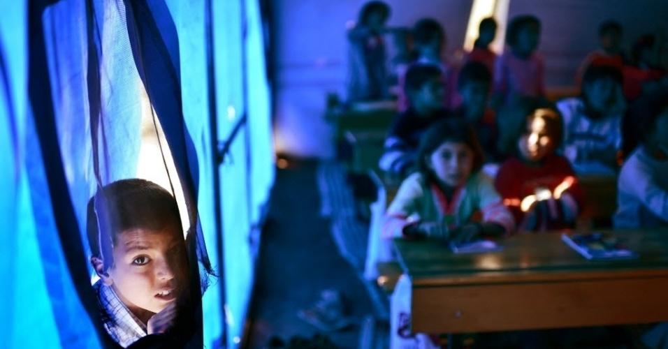 10.nov.2014 - Uma escola foi improvisada no centro de refugiados para sírios curdos em Suruc, na fronteira turca com a Síria. A Turquia tem mantido uma política de portas abertas para todos aqueles que fogem do avanço da milícia radical do Estado Islâmico. Mais de 1,5 milhões de sírios entraram no país vizinho, sendo que mais de 280 mil estão em campos de refugiados