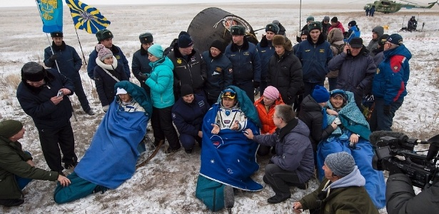 O engenheiro de voo Alexander Gerst da ESA, o comandante Max Suraev da Roscosmos e o engenheiro de voo da Nasa Reid Wiseman sentam-se em cadeiras após saírem da cápsula Soyuz TMA-13M