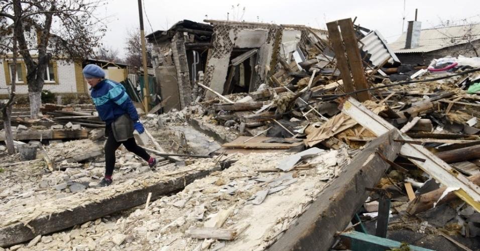 11.nov.2014 - Mulher coleta pertences remanescentes em sua casa, destruída em conflito entre forças ucranianas e rebeldes pró-Rússia, em Donetsk, no leste da Ucrânia. Os Estados Unidos advertiram a Rússia de que, se não rever seu empenho em