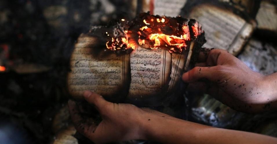 12.nov.2014 - Homem palestino exibe uma cópia do livro sagrado do Islã, o Alcorão, queimando dentro de uma mesquita que foi incendiada por colonos israelenses em al-Mughayir, na Cisjordânia, nesta quarta-feira (12). Colonos israelenses incendiaram o local em um suposto ato de vingança, após um ataque palestino matar um soldado israelense em Tel Aviv na terça-feira