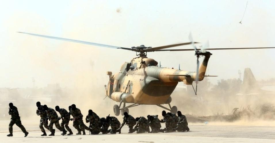 12.nov.2014 - Militares líbios mostram suas habilidades durante uma cerimônia de graduação na base aérea de Trípoli, na capital Líbia, nesta quarta-feira (12). Três anos depois de o ditador Muammar Gaddafi ser derrubado e morto em uma revolta apoiada pela Otan, a Líbia é inundada com armas e pmilícias, e é administrada por governos rivais e parlamentos