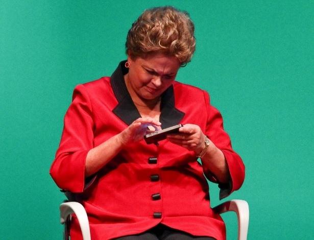 A presidente Dilma Rousseff mexe no telefone do ministro Afif Domingos (Micro e Pequena Empresa), durante evento em 2014