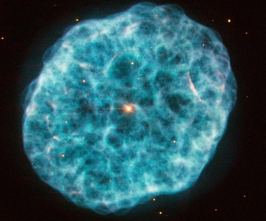 13.nov.2014 - Imagem obtida pelo telescópio Hubble, da Nasa (agência espacial americana), mostra a nebulosa NGC 1501,também conhecida como nebulosa da ostra, localizada na constelação da Girafa. Com nuvens irregulares e repleta de regiões acidentadas, a nebulosa possui uma estrela central brilhante, que pode ser visto facilmente nesta imagem. Ainda que estrelas variáveis não sejam incomuns, é raro encontrar uma no coração de uma nebulosa planetária. Descoberta por William Herschel em 1787, NGC 1501 é uma nebulosa planetária que está a pouco menos de 5.000 anos-luz de distância
