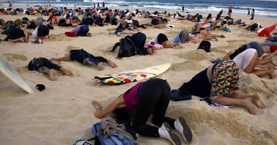 """13.nov.2014 - Um grupo de aproximadamente 400 manifestantes enterraram a cabeça na areia da praia de Bondi, em Sydney, na Austrália. O protesto é um alerta para os líderes que se reúnem durante a cúpula do G20, que acontece em Brisbane, na Austrália, a partir do próximo sábado (15). Os manifestantes questionaram a postura ambiental do primeiro-ministro australiano Tony Abbott, argumentando que ele """"tem a cabeça enterrada na areia"""" no que se refere a mudanças climáticas"""