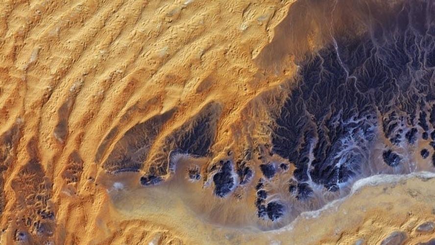14.nov.2014 - Esta imagem de satélite foi capturada sobre o sudeste da Argélia, no coração do deserto do Saara. Ela mostra uma grande área de formação rochosa, que aparece na cor roxa no lado inferior direito, com padrões de erosão fluvial so período em que a região recebia maior quantidade de chuvas. Atualmente, esta área registra uma média de cerca de 10 mm de chuva por ano. Dunas de areia desenhadas pelo vento são visíveis do lado esquerdo. A área na parte inferior parece ser plana, com pequenas manchas de vegetação