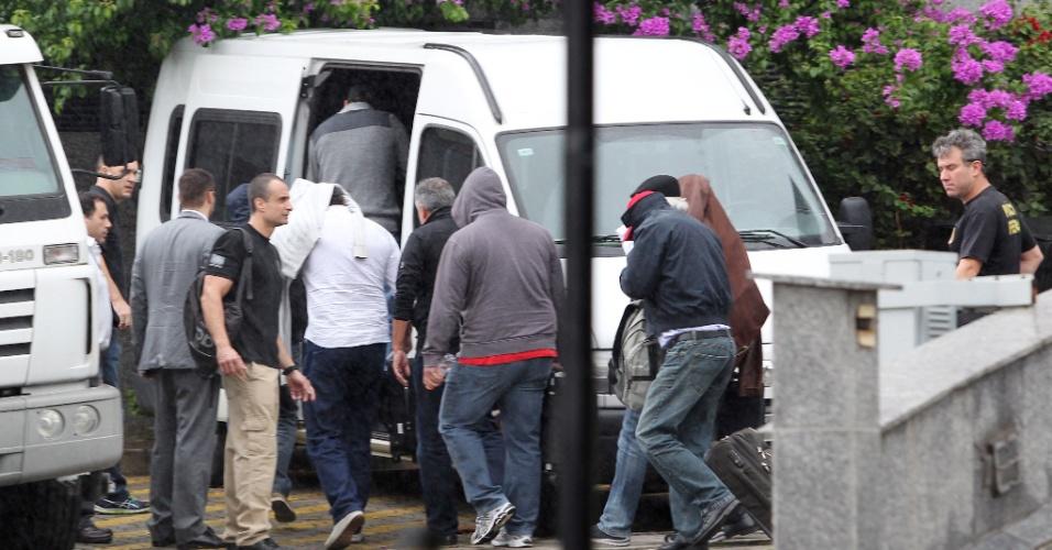 14.nov.2014 - Na sede da Superintendência da PF (Polícia Federal), policiais conduzem os onze presos detidos na operação que aconteceu em vários Estados brasileiros nesta sexta-feira (14). Os detidos foram levados para o aeroporto de Guarulhos, de onde serão transferidos para Curitba