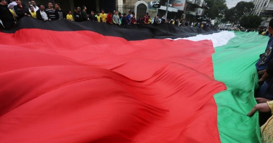 14.nov.2014 - Pelestinos carregam bandeira de 100 metros de comprimento durante passeata na cidade de Nablus, na Cisjordânia. Eles celebram os 10 anos da morte do líder palestino Yasser Arafat e reafirmam a independência do país, reconhecida pela. Arafat, morto aos 75 anos, teve importância fundamental na criação do Estado Palestino, através de sua atuação na OLP (Organização para Libertação da Palestina)