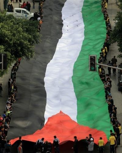 14.nov.2014 - Pelestinos carregam bandeira de 100 metros de comprimento durante passeata na cidade de Nablus, na Cisjordânia. Eles celebram os 10 anos da morte do líder palestino Yasser Arafat e reafirmam a independência do país, reconhecida pela. Arafat, morto aos 75 anos, teve importância fundamental na criação do Estado Palestino, através de sua atuação na OLP (Organização para Libertação da Palestina), em em tratados de paz assinados com Israel - que foram insuficientes para a resolução de conflitos