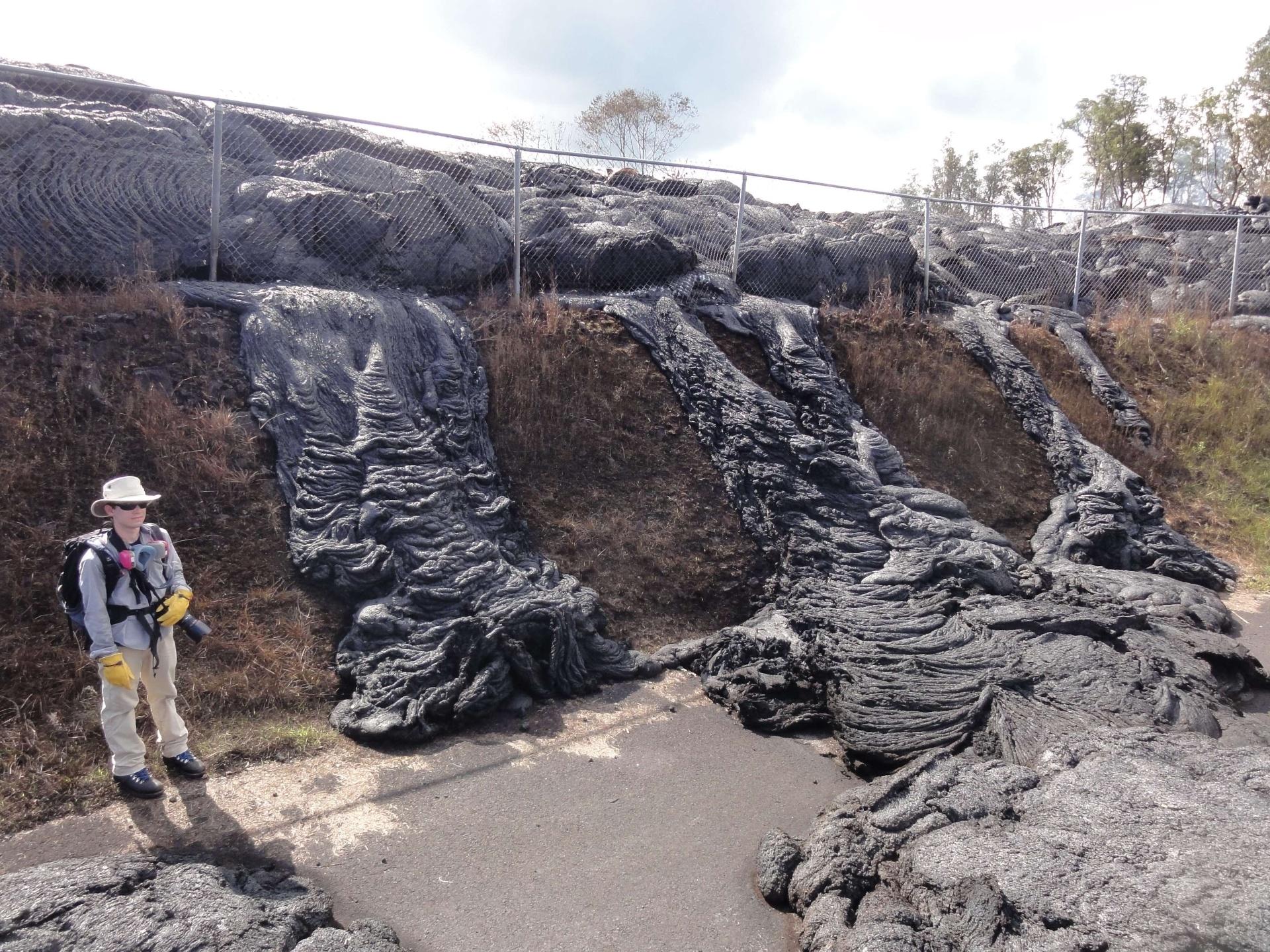 16.nov.2014 - Pesquisador fica próximo a lava seca do vulcão Kilauea, em Pahoa, no Havaí. O fluxo de lava do vulcão alcançou a cerca da estação de transferência, queimando o alfalto por vários dias