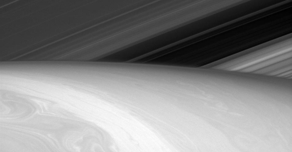 17.nov.2014 - Imagem obtida pela sonda Cassini, da Nasa (agência espacial americana), mostra o lado iluminado dos anéis de Saturno e a superfície do planeta, resultado da dinâmica de fluídos. Os astrônomos estudam a dinâmica das nuvens do planeta para entender a compreensão dos fluxos de fluídos do planeta. Os astrônomos acreditam que a descoberta será útil para compreender nossa própria atmosfera e de outros planetas