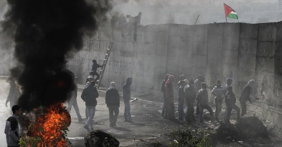 17.nov.2014 - Manifestantes palestinos queimam pneus e tentam abrir um buraco em um muro que separa a cidade de Abu Dis de Jerusalém. Um motorista de ônibus palestino foi encontrado enforcado em seu veículo em Jerusalém. A polícia israelense afirma que se trata de suicídio