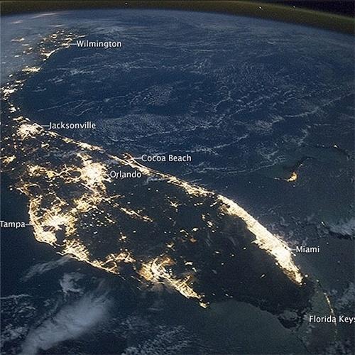 18.nov.2014 - 18.nov.2014 - Os astronautas a bordo da Estação Espacial Internacional (ISS) registraram uma foto do Estado da Flórida (EUA), em outubro de 2014. A península é altamente reconhecível, mesmo à noite. Áreas iluminadas permitem perceber os tamanhos das cidades. A mais brilhante é a área metropolitana de Miami, a maior área urbana do sudeste do país, e lar de 5,6 milhões de pessoas. A segunda maior área é a região de Tampa Bay (com 2,8 milhões de pessoas) na costa do golfo da península. Orlando, localizada no meio, é um pouco menor (2,3 milhões). As áreas azuis em toda a imagem são nuvens iluminadas pelo luar