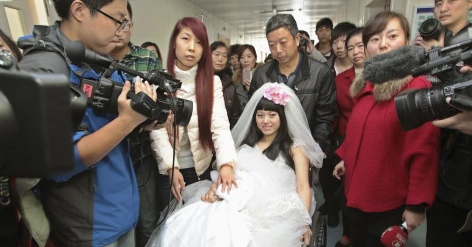 18.nov.2014 - A noiva Fan Huixiang (C), jovem de 25 anos de idade que sofre de câncer terminal, senta-se em uma cadeira de rodas empurrada por seu pai, durante sua cerimônia de casamento realizada em um hospital em Zhengzhou, província de Henan, na China