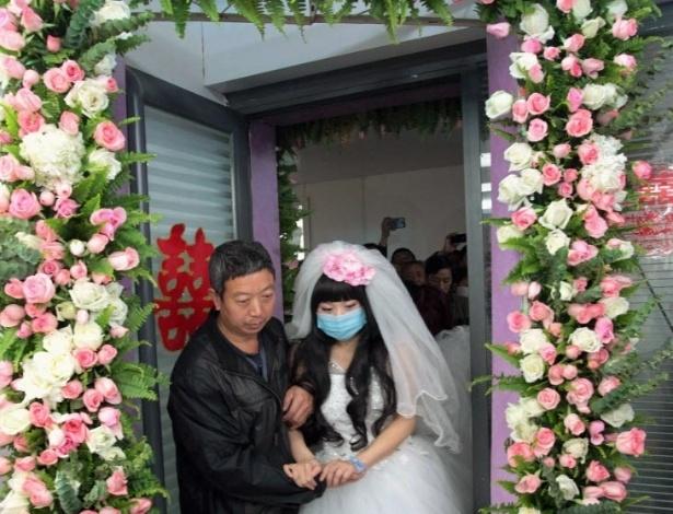 18.nov.2014 - A noiva Fan Huixiang, uma paciente 25 anos de idade, é ajudada por seu pai durante seu casamento em um hospital em Zhengzhou, na província de Henan, na China. Fan foi diagnosticada com um tumor maligno em sua vértebra torácica em junho deste ano, já estando em fase final. Ela e seu marido Yu Haining, 24, realizaram uma cerimônia de casamento no hospital no dia 17 de novembro, depois de cinco anos de relacionamento