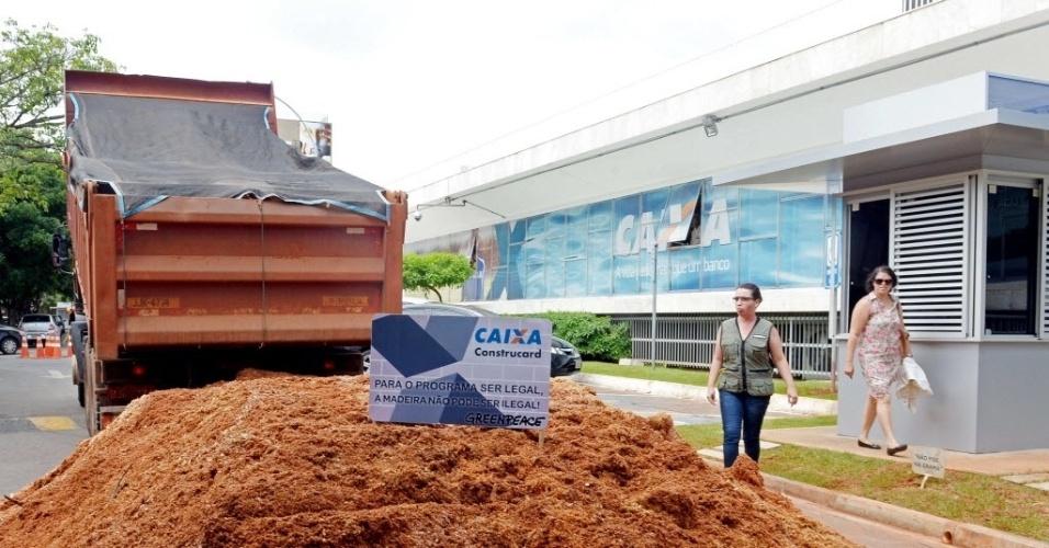 18.nov.2014 - Ativistas do Greenpeace despejaram duas toneladas de serragem em frente à sede do banco estatal Caixa Econômica, em Brasília, em protesto para o financiamento de empresas que praticariam a extração ilegal de madeira na floresta amazônica