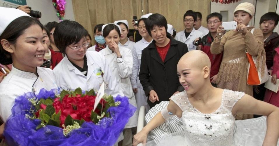 18.nov.2014 - Enfermeiros entregam um buquê de flores para a paciente Fan Huixiang, que sofre de câcer terminal, antes de sua cerimônia de casamento em um hospital em Zhengzhou, província de Henan, na China