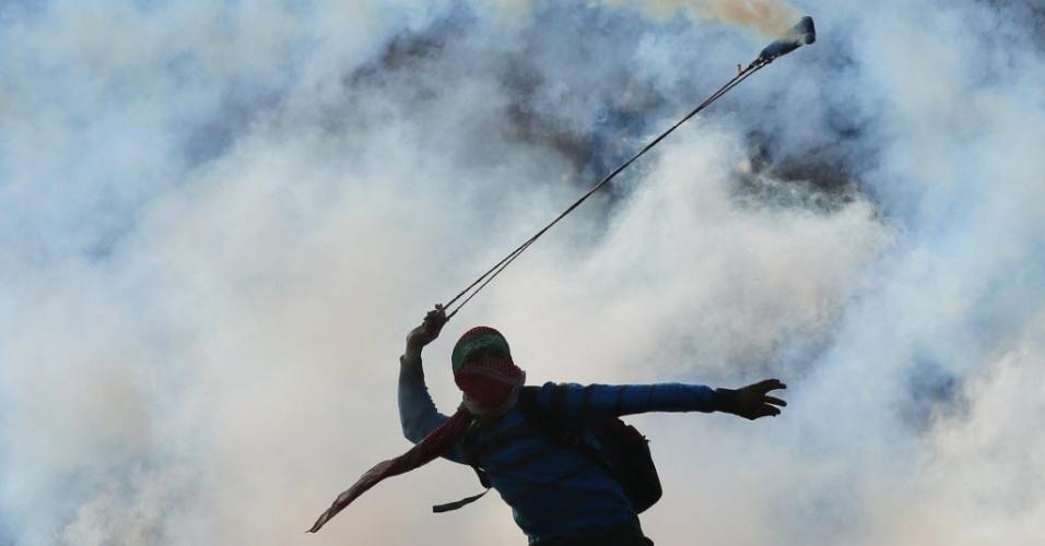 18.nov.2014 - Jovem palestino mascarado vestindo uma lenço do Hamas na cabeça usa estilingue para atirar bomba de gás lacrimogêneo na direção de forças israelenses nos arredores da prisão militar israelense de Ofer, perto da cidade de Ramallah, na Cisjordânia