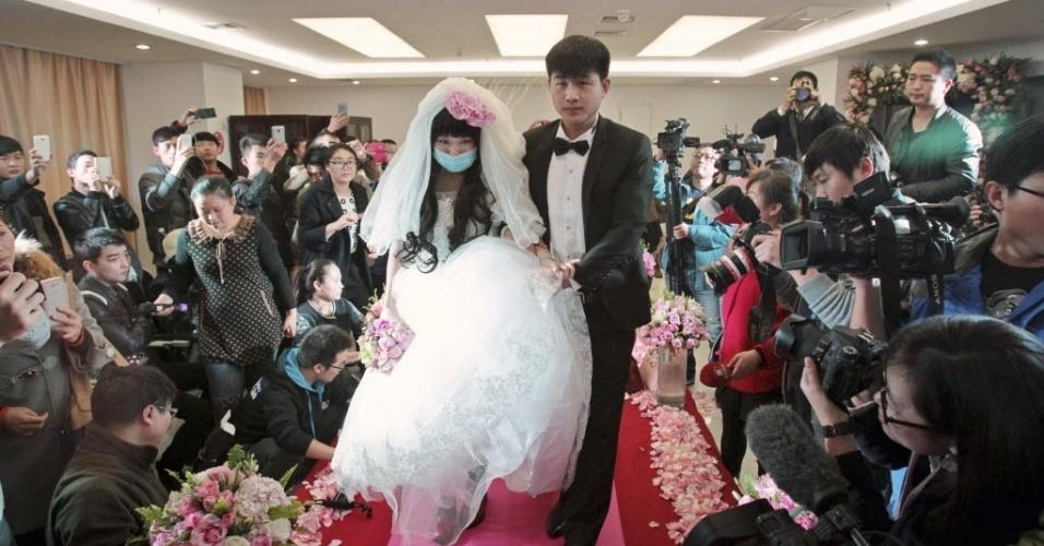 18.nov.2014 - Vestindo uma máscara, a noiva Fan Huixiang anda no tapete vermelho com seu noivo Yu Haining, 24, após se acasarem em um hospital em Zhengzhou, província de Henan, na China