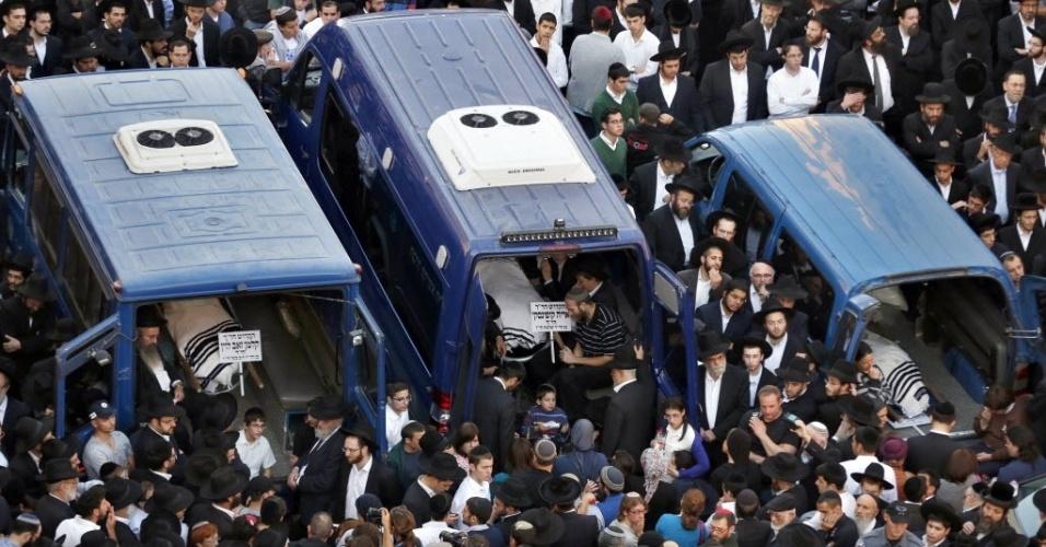 18.nov.2014- Os corpos de Aryeh Kopinsky (centro), Calman Levine (esq.) e Avraham Shmuel Goldberg (dir.) são levados em veículos funerários próximo ao local do ataque contra uma sinagoga de Jerusalém, realizado por dois palestinos armados com armas e machados, que culminou na morte de quatro israelenses