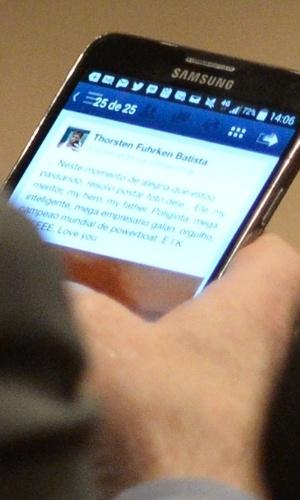 O empresário Eike Batista lê a mesnagem do filhor Thor no Facebook, antes da audiência no Tribunal de Justiça Federal